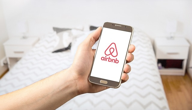 Hand holding phone reading Airbnb