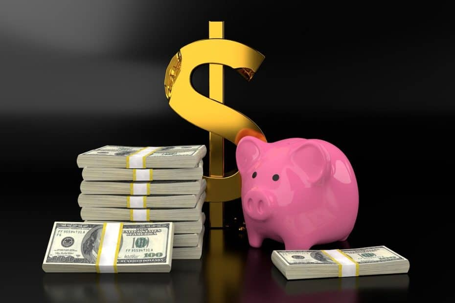 Pink piggy bank with large gold dollar sign and stacks of $100-bills on a black background