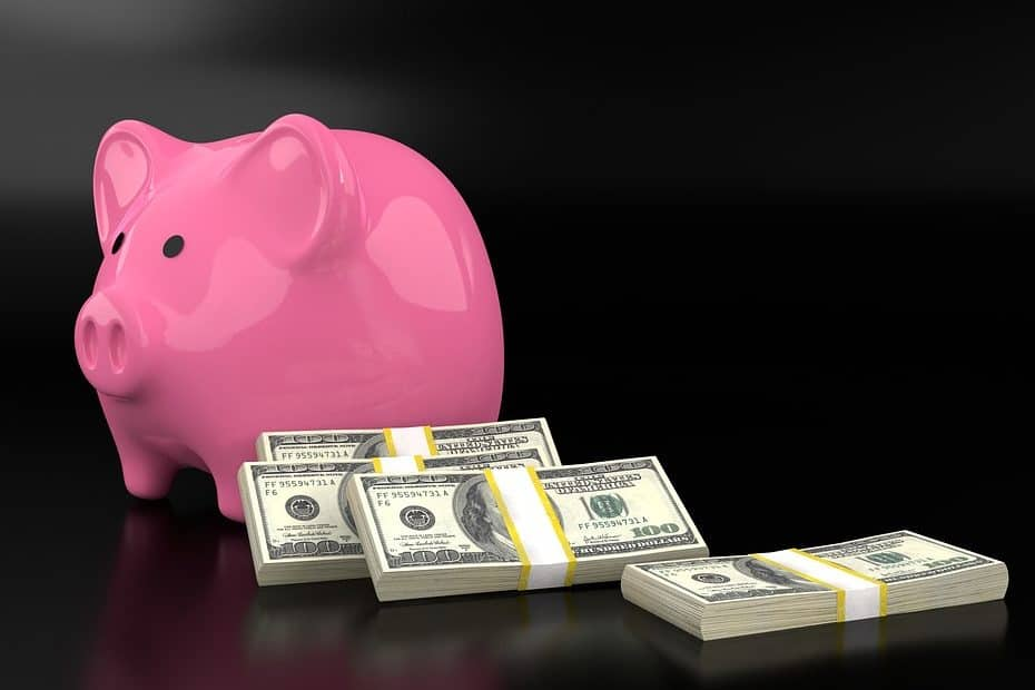 Pink piggy bank with 4 bundles of $100 bills, on a black background