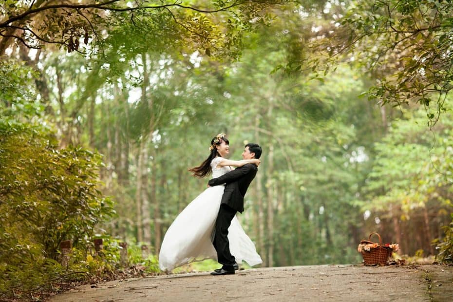 Bride and groom embracing on a path in the woods