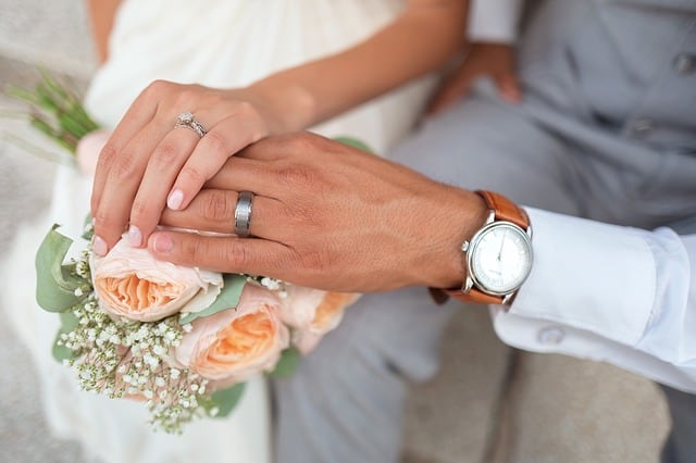 Closeup of the hands of the bride and groom, showing their rings and bouquet of roses