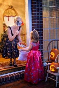 Girl trick-or-treating in a pink dress, woman with candy bowl