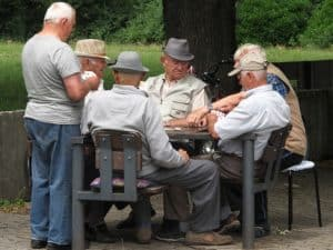 A group of 6 senior men playing cards at an outdoor table