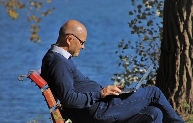 Senior man sitting by the lake with a laptop