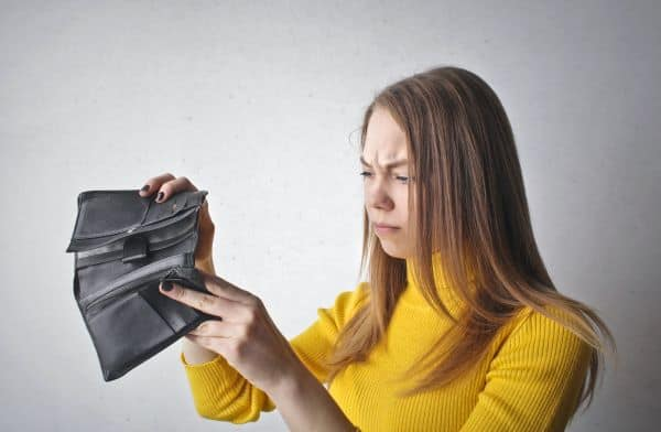 Low income budget, woman looking into empty wallet